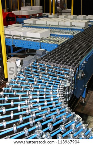 Conveyor rollers at box packing line in factory - stock photo