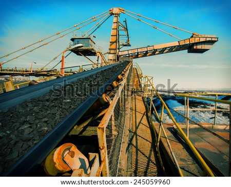 conveyor transport for loading iron ore from the warehouse - stock photo