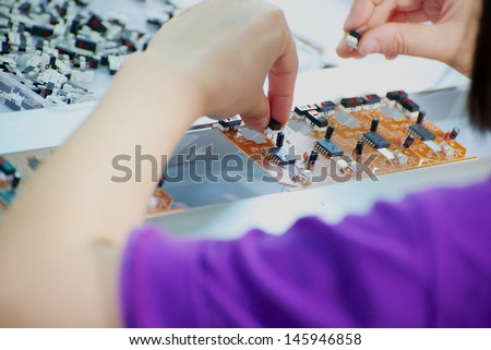 conveyor worker hand made assembling electronic device on Chinese factory - stock photo