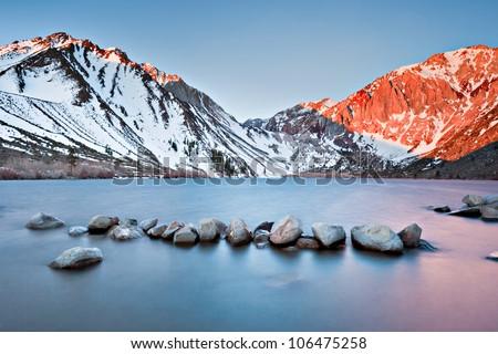 Convict Lake in the Eastern Sierras glows with the colors of sunrise early one winter morning. - stock photo