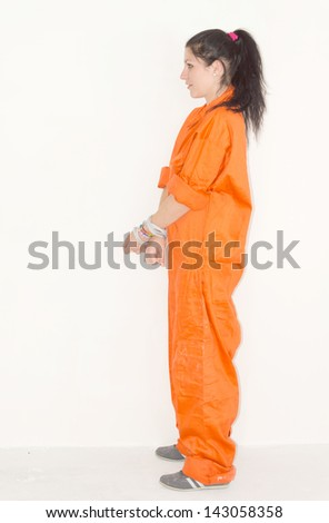 Convict woman in handcuffs and orange jumpsuit with a look of hopelessness - stock photo