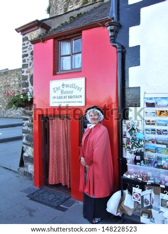 CONWAY, GREAT BRITAIN - CIRCA AUGUST 2007: Unknown woman stands near  the smallest house in Great Britain on August 2007 in Conway, Great Britain.