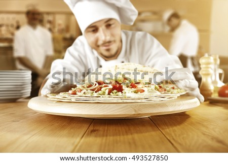 cook chef in kitchen and few men on blurred background