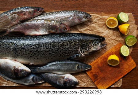 Cook expensive fish restaurant prepares lunch pasta with shrimp, baked sea bass and Dourado, next to the fish is lemon-lime, fish lies neatly on parchment paper - stock photo