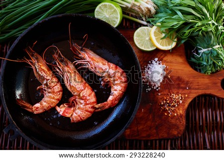 Cook fried king prawns for the fresh shrimp salad onion and tomato. Three large shrimp fried in rapid fire a few minutes and fed to a hot salad - stock photo