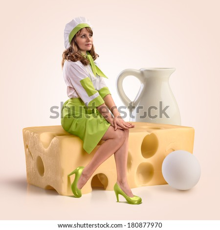 cook girl sitting on a piece of cheese on a beige background - stock photo