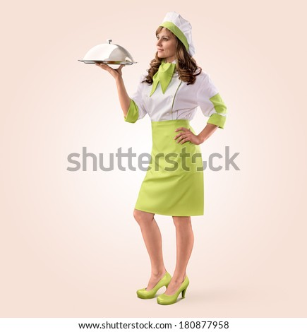 cook girl with restaurant cloche or food tray on a beige background - stock photo