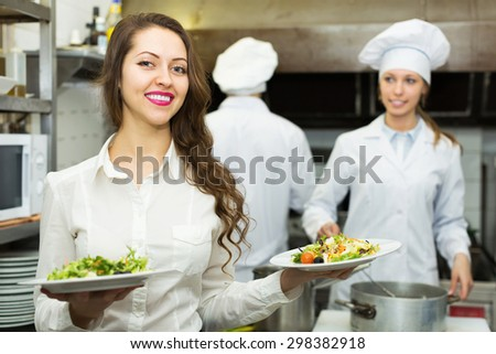 Cook gives to woman waitress plates with prepared meal at restaurant kitchen - stock photo
