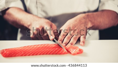 Cook hands cutting fresh salmon fillet close-up