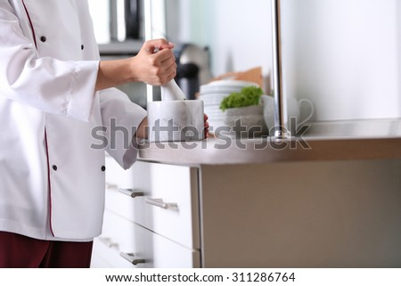 Cook hands with mortar with herbs on bright background - stock photo
