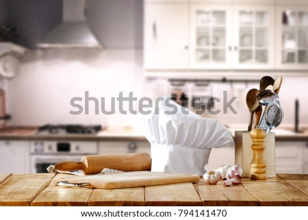 Cook hat and wooden table with kitchen furniture