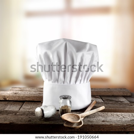 cook hat wooden spoons and window of sunlight  - stock photo