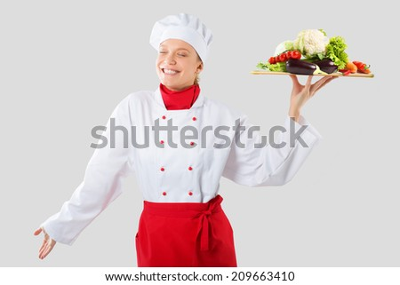 cook holds in one hand a wooden tray. Cook with mountain prohibited vegetables  - stock photo