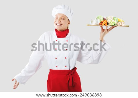cook holds in one hand a wooden tray. Cook with vegetables - stock photo