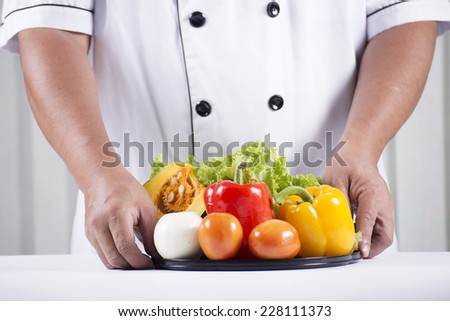 cook holds tray of vegetable for prepared making salad.