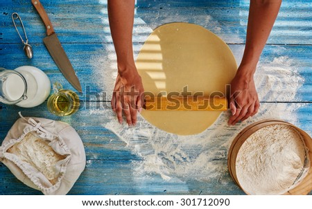 Cook in a trendy Italian restaurant rolls the dough to cook from Spaghetti, Girl Roll out the dough to cook from it that pie fillings or pizza - stock photo