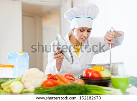 Cook in white hat looks into the pan in kitchen