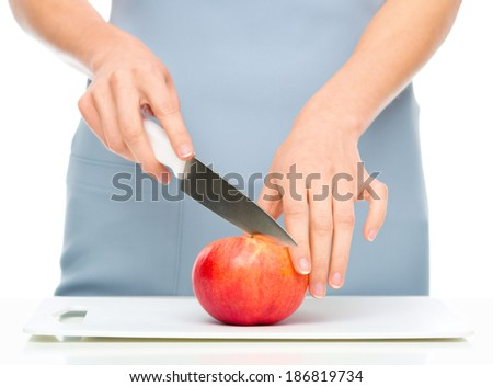 Cook is chopping apple, closeup shoot, isolated over white - stock photo