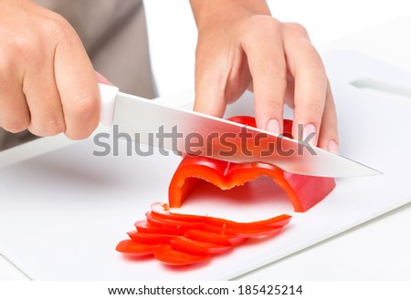 Cook is chopping bell pepper, closeup shoot, isolated over white - stock photo