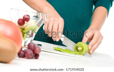 Cook is chopping kiwi for fruit dessert, closeup shoot, isolated over white - stock photo