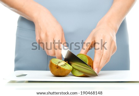 Cook is chopping kiwi fruit, closeup shoot, isolated over white - stock photo