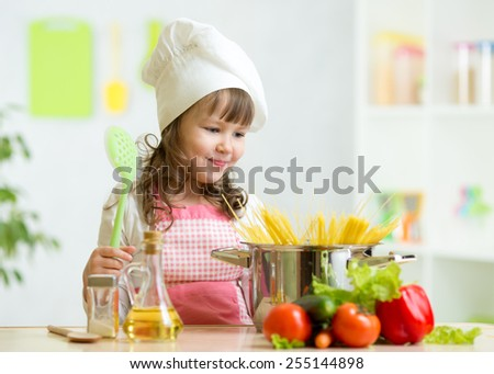 Cook kid girl makes healthy vegetables meal in the kitchen - stock photo