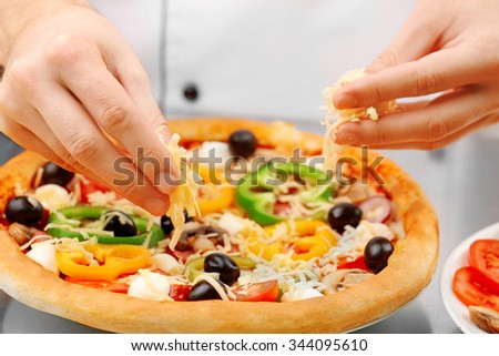 Cook making delicious pizza at the restaurant, close-up - stock photo