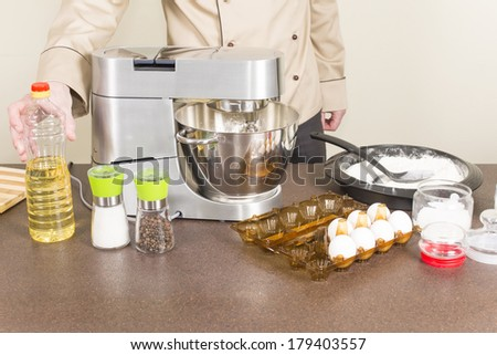 cook prepares dough for pancakes on a food processor