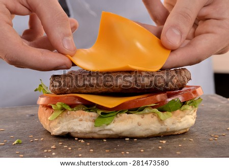 Cook preparing cheese burger. - stock photo