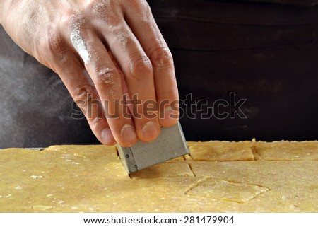 Cook preparing cookies dough using mold. - stock photo