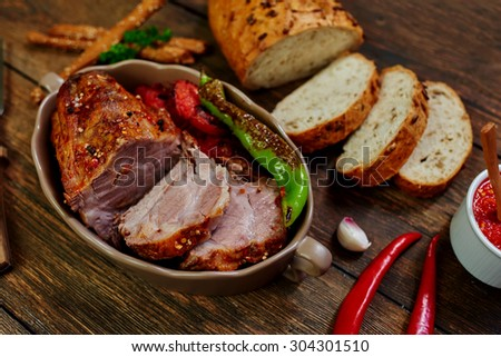 Cook pulled out of the oven a piece of lamb tenderloin, served it with grilled vegetables in ceramic ware, a number of fresh crusty bread and a sauce made from cherry tomatoes and chili peppers - stock photo