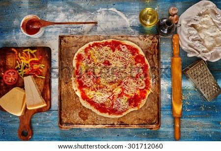 Cook pulled the pan out of the oven which has a pizza on the table next to the board for cutting vegetables for her a few kinds of cheese, and the remaining stuffing - stock photo