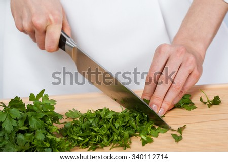 Cook's hands chopping fresh parsley on wooden board