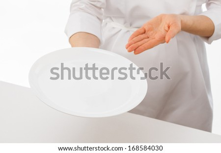 Cook showing an empty plate on white background - stock photo