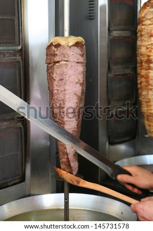 Cook Slicing Turkish Lamb Doner Kebab with a Sharp Sword like Knife