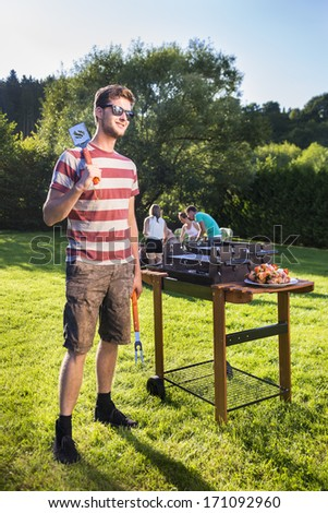 Cook standing in the park next to his grill with his friends in the background in the summer - stock photo