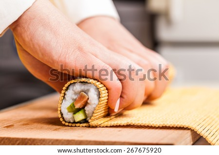 cook turns nori sheet with filling in the roll closeup - stock photo
