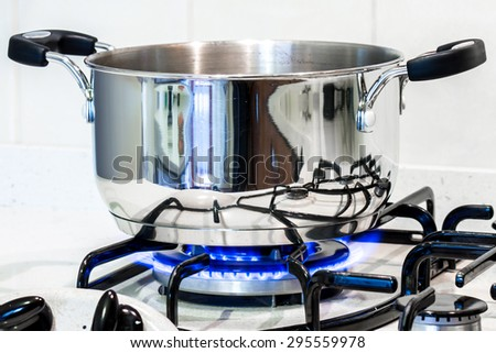cook with a steel pot on the stove in the kitchen - stock photo