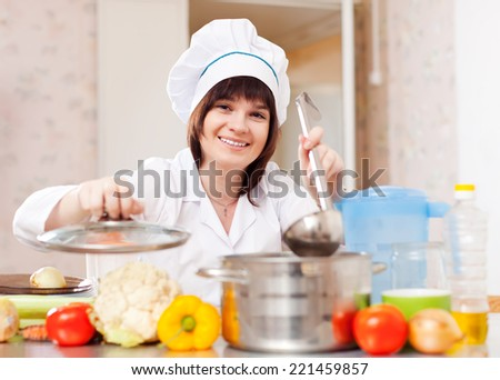 cook woman in toque cooks from vegetables with ladle in kitchen