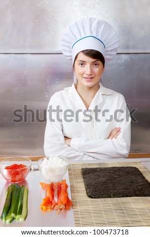 Cook woman with Ingredients for making sushi rolls - stock photo