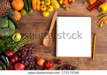 Cookbook. Copy space / studio photography of open blank ring bound notebook surrounded by a fresh vegetables and pencil on old wooden table  - stock photo