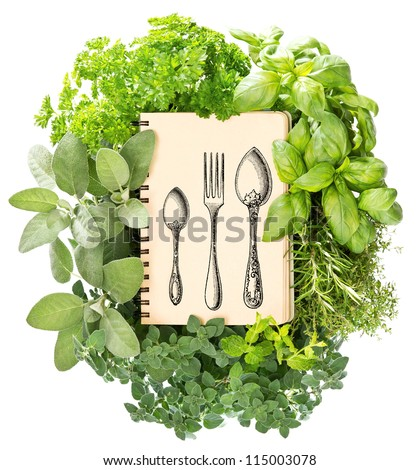 cookbook with variety fresh herbs over white background