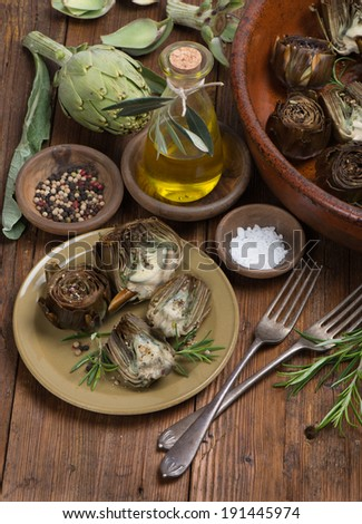 Cooked and fresh artichokes with olive oil, pepper and salt on the wooden table  - stock photo