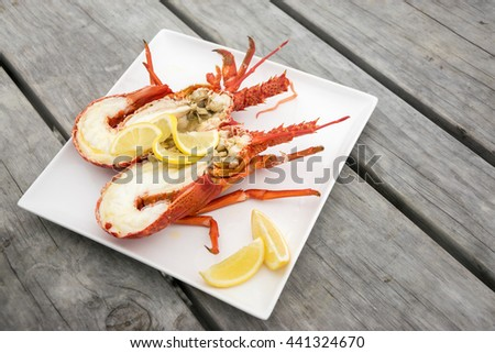 Cooked and halved New zealand crayfish on the wooden table. - stock photo