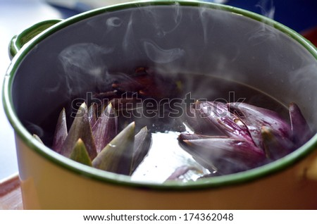 Cooked Artichoke in a pot. - stock photo