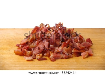 cooked bacon bits on wooden chopping  board - stock photo