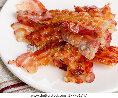 Cooked bacon rashers on a white plate. Selective focus