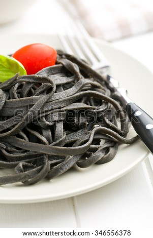 cooked black noodles with squid sepia ink on plate - stock photo