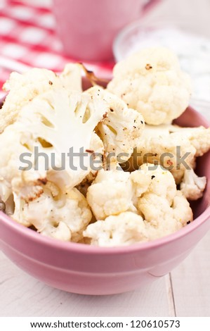 Cooked cauliflower florets with sauce vertical