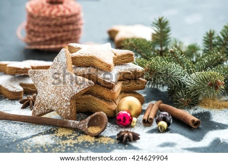 Cooked Christmas holiday traditional gingerbread cookies with sugar powder and cinnamon sticks on black background, selective focus - stock photo